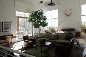 ベッドルームも天井が高く、天井からプロジェクターが吊るされ、壁に写される。使われるソファはヴィンテージ物。