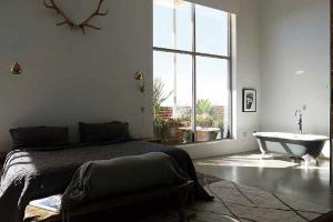 ベッドの脇のオープンスペースには猫足のバスタブが置かれる。