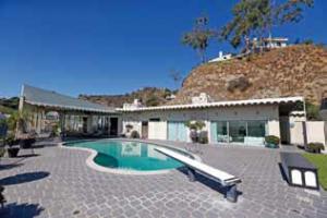 平屋 の住宅にビーンズのような形のプール。LA のプールはとても深く、飛び込 み台が備えられている。